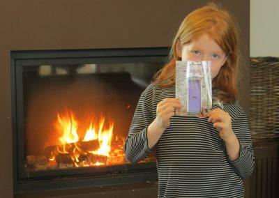 meisje met foto voor het vuur