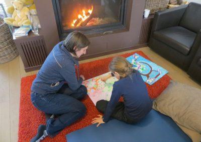 mama en dochter tonen tekeningen voor het vuur