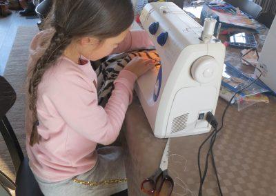 meisje naait mantel met naaimachine